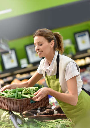 ejotes: empleado de supermercado poner las verduras en las estanterías