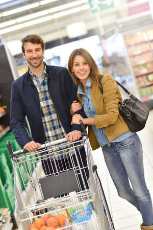 Couple pushing shopping cart in supermarket Stock Photo