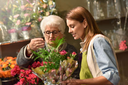 arranging: Senior woman in flower shop with florist Stock Photo