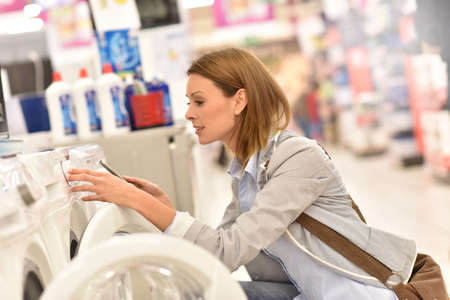 technical department: Woman in supermarket comparing washing machine details with smartphone
