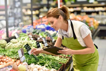 dipendente Supermercato mettere le verdure in scaffali Archivio Fotografico