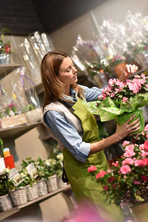 selling service: Woman working in flower shop Stock Photo