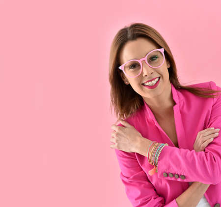 30 to 35 years old: Cheerful girl wearing eyeglasses, pink color Stock Photo