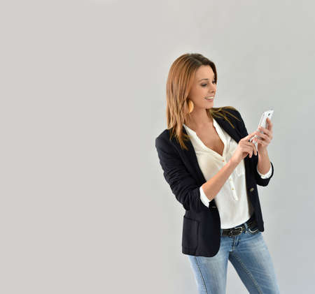 30 years old woman: Beautiful trendy woman using smartphone, grey background
