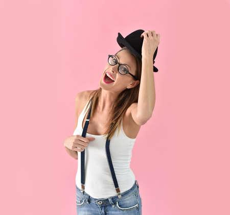 fashion background: Fashion girl with hat and eyeglasses, isolated on pink background Stock Photo