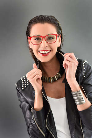 30 to 35 years old: Beautiful trendy woman with red eyeglasses, grey background Stock Photo