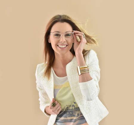 glasses model: Trendy girl with eyeglasses, beige background Stock Photo