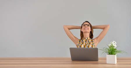 relajado: Mujer hermosa en la oficina que estira los brazos detrás de la cabeza, aislado