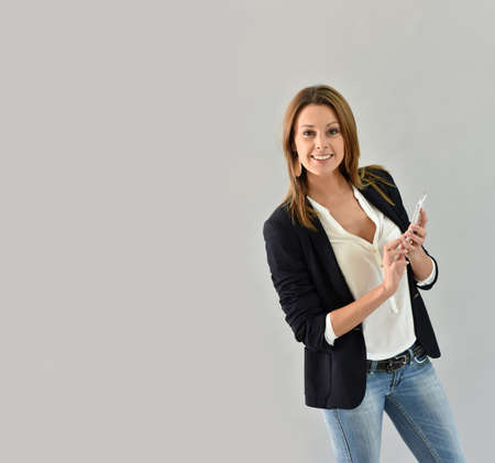 35 years old: Beautiful trendy woman using smartphone, grey background