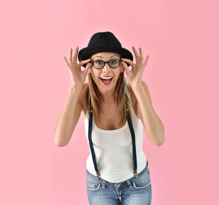 glasses model: Fashion girl with hat and eyeglasses, isolated on pink background Stock Photo