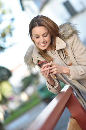 sending: Trendy girl in city street sending text message with smartphone Stock Photo