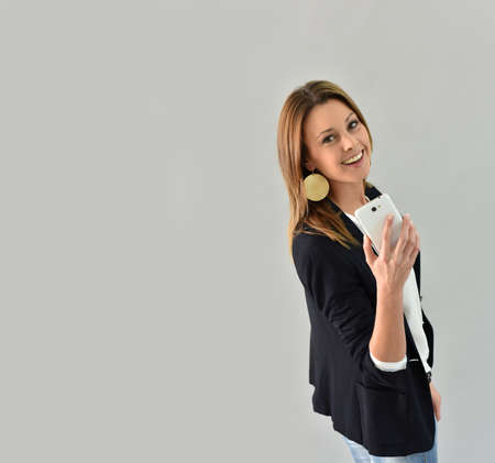 30 to 35 years old: Beautiful trendy woman using smartphone, grey background