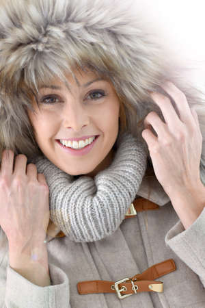 30 to 35 years old: Closeup of woman wearing jacket with fur hood, isolated Stock Photo