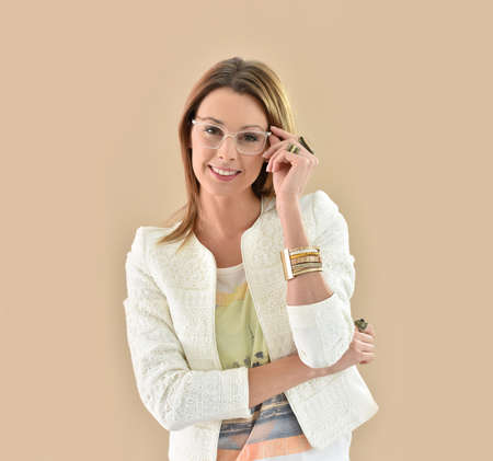 eyewear: Trendy girl with eyeglasses, beige background Stock Photo