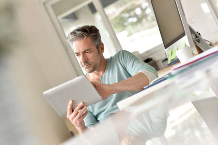 casual attire: Man in office working on digital tablet