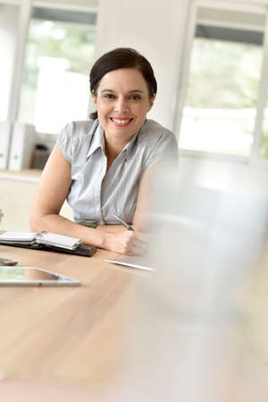 fourties: Businesswoman in meeting room writing on agenda