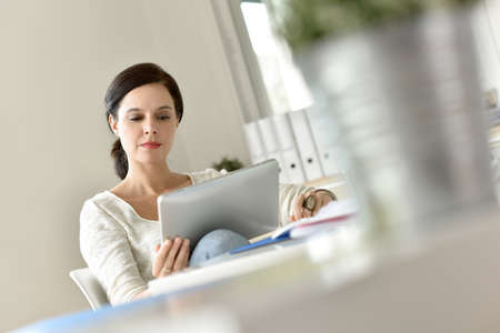 business casual: Businesswoman in office working on digital tablet