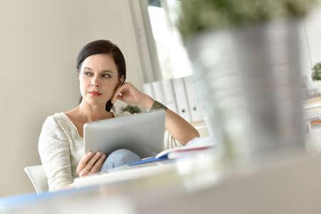 persona pensando: Empresaria en la oficina trabajando en la tableta digital