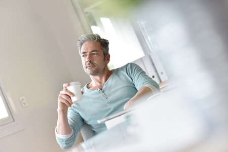 business project: Man in office relaxing with cup of coffee