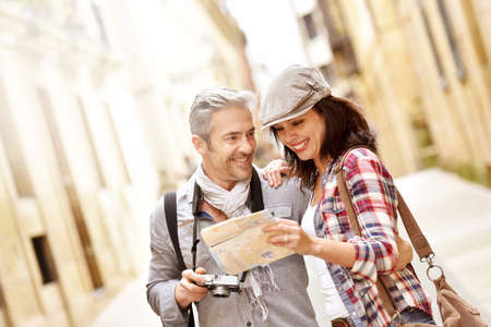 person reading: Cheerful couple looking at map, week-end tour