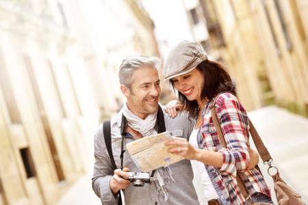 persona leyendo: pareja alegre mirando el mapa, gira de fin de semana