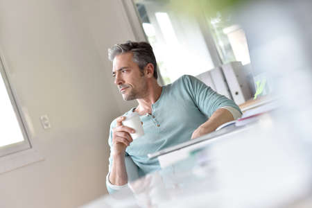 fourties: Man in office relaxing with cup of coffee
