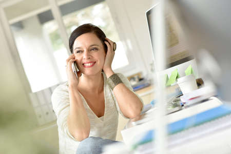woman at the phone: Woman in office talking on phone