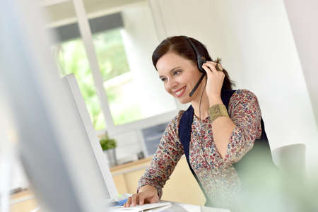 casual attire: Beautiful teleoperator in office using phone headset