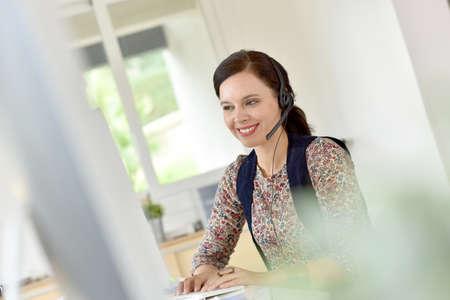 teleoperator: Beautiful teleoperator in office using phone headset