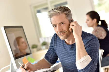 hombres maduros: Hombre de negocios en la oficina hablando por teléfono