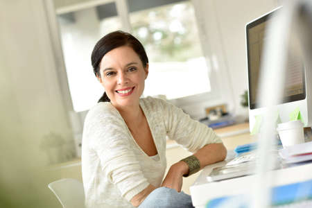 casual attire: Portrait of smiling woman in office