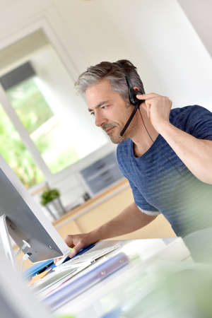 teleconference: Businessman in office using phone headset
