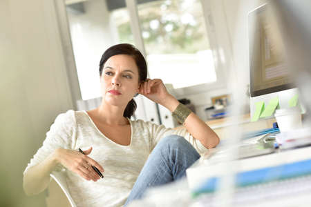 Woman in office with a thoughtful look Foto de archivo