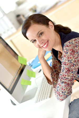 desktop computers: Portrait of smiling woman working in office Stock Photo