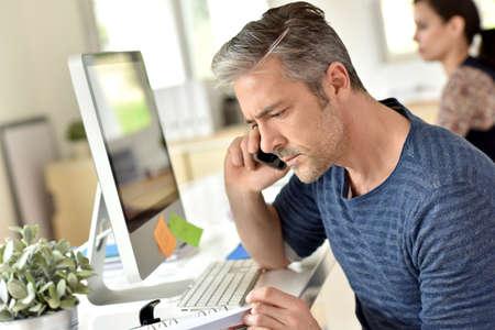 personas dialogando: Hombre de negocios en la oficina hablando por teléfono