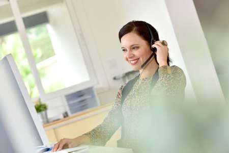 business center: Beautiful teleoperator in office using phone headset