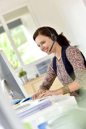 teleoperator: Beautiful teleoperator in office using phone headset