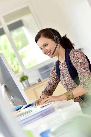 fourties: Beautiful teleoperator in office using phone headset