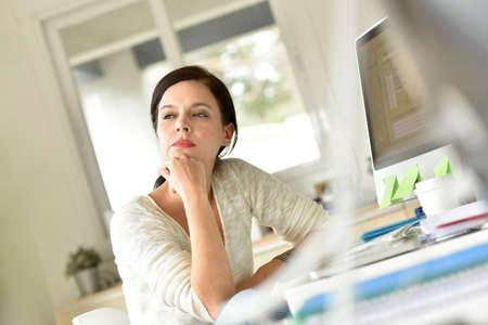 persona pensando: Mujer en la oficina con una mirada reflexiva