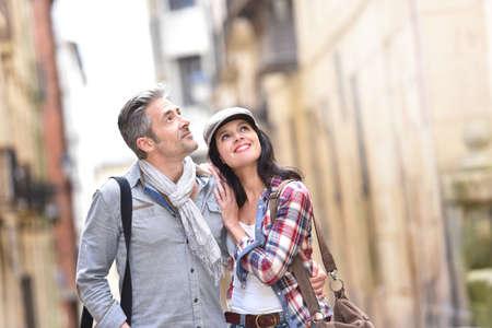 スペインの歴史的な地区を歩く観光客のカップル 写真素材