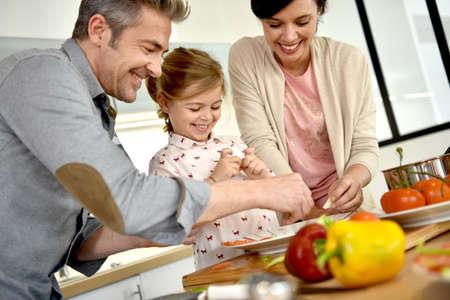 Ouders met een kind samen koken thuis