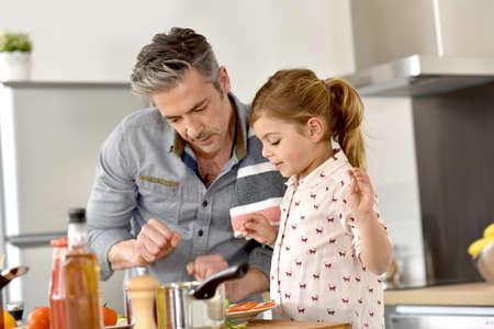 niños cocinando: Padre con la niña cocinar juntos en la cocina Foto de archivo