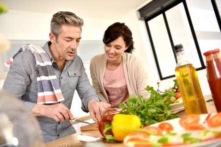 Echtpaar van middelbare leeftijd met plezier samen koken