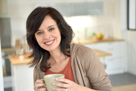 Mujer madura sonriente en su casa de beber té
