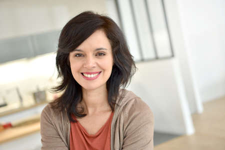 Portret van lachende 40-jarige vrouw thuis Stockfoto
