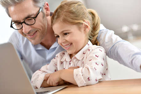 40 to 45 years old: Man with little girl using laptop computer Stock Photo