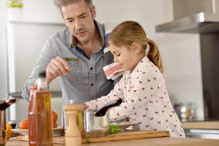 Padre con la bambina cucinare insieme in cucina