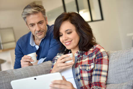 couple relaxing: Couple at home websurfing with digital tablet