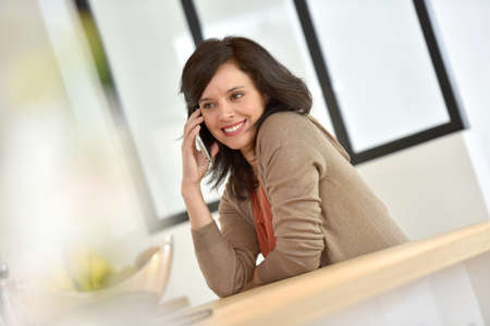 woman at the phone: Middle-aged woman in kitchen talking on phone