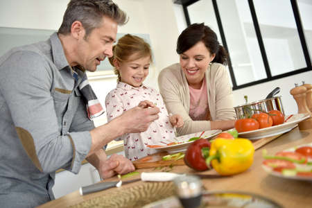 kids meal: Parents with child cooking together at home